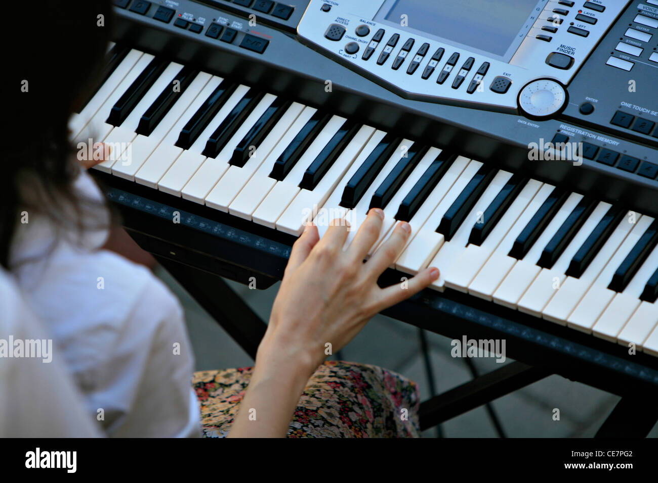 girl learning to play synthesizer - Stock Image