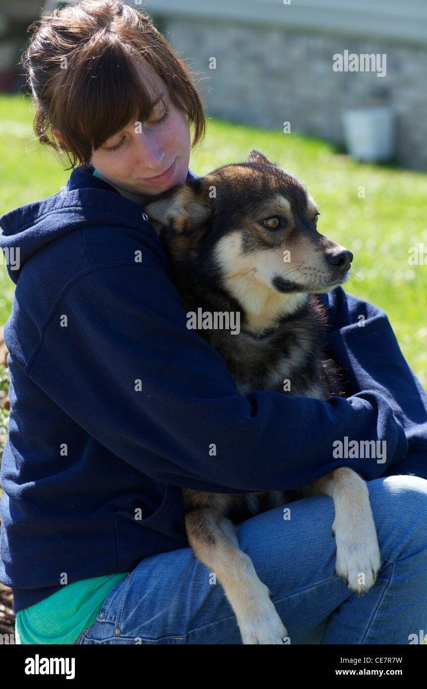girl holding dog that is half coyote - Stock Image