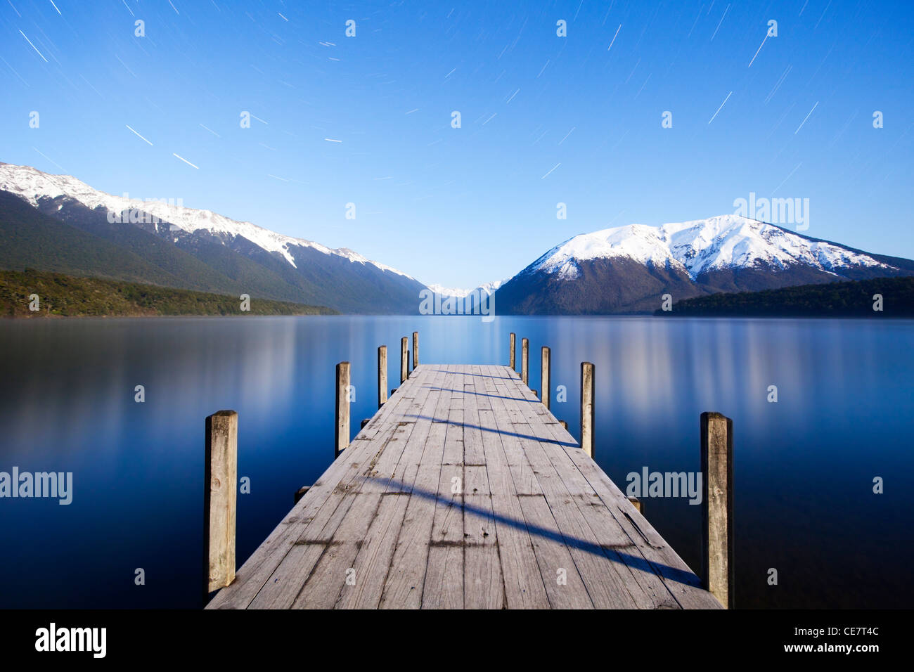 The jetty at Lake Rotoiti, Nelson Lakes National Park, New Zealand, by moonlight. Star trails can be see in the - Stock Image