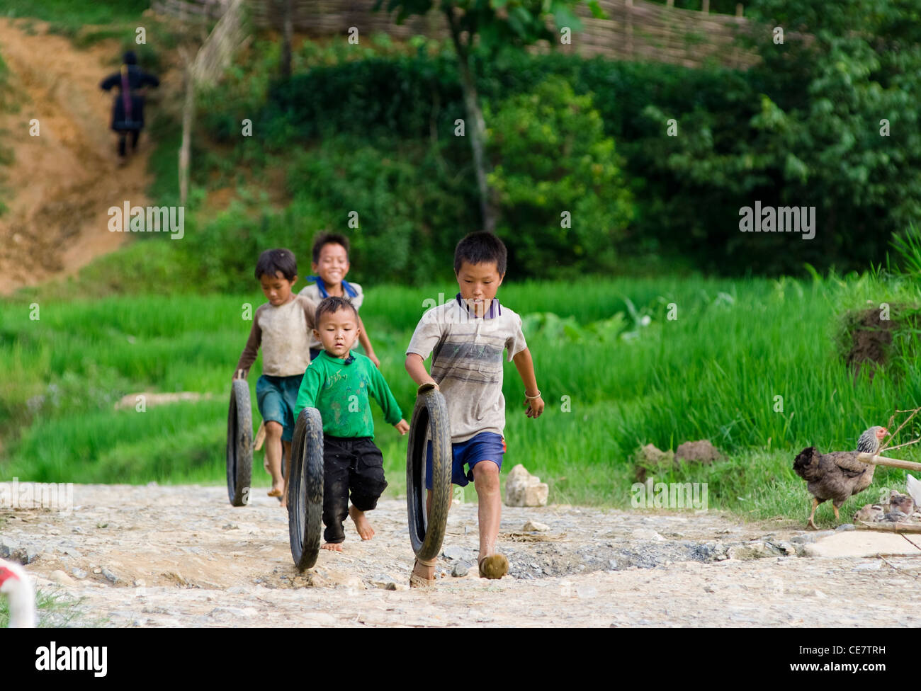 Hilltribe boys enjoy tire-spinning competition  in Sapa, Vietnam. - Stock Image
