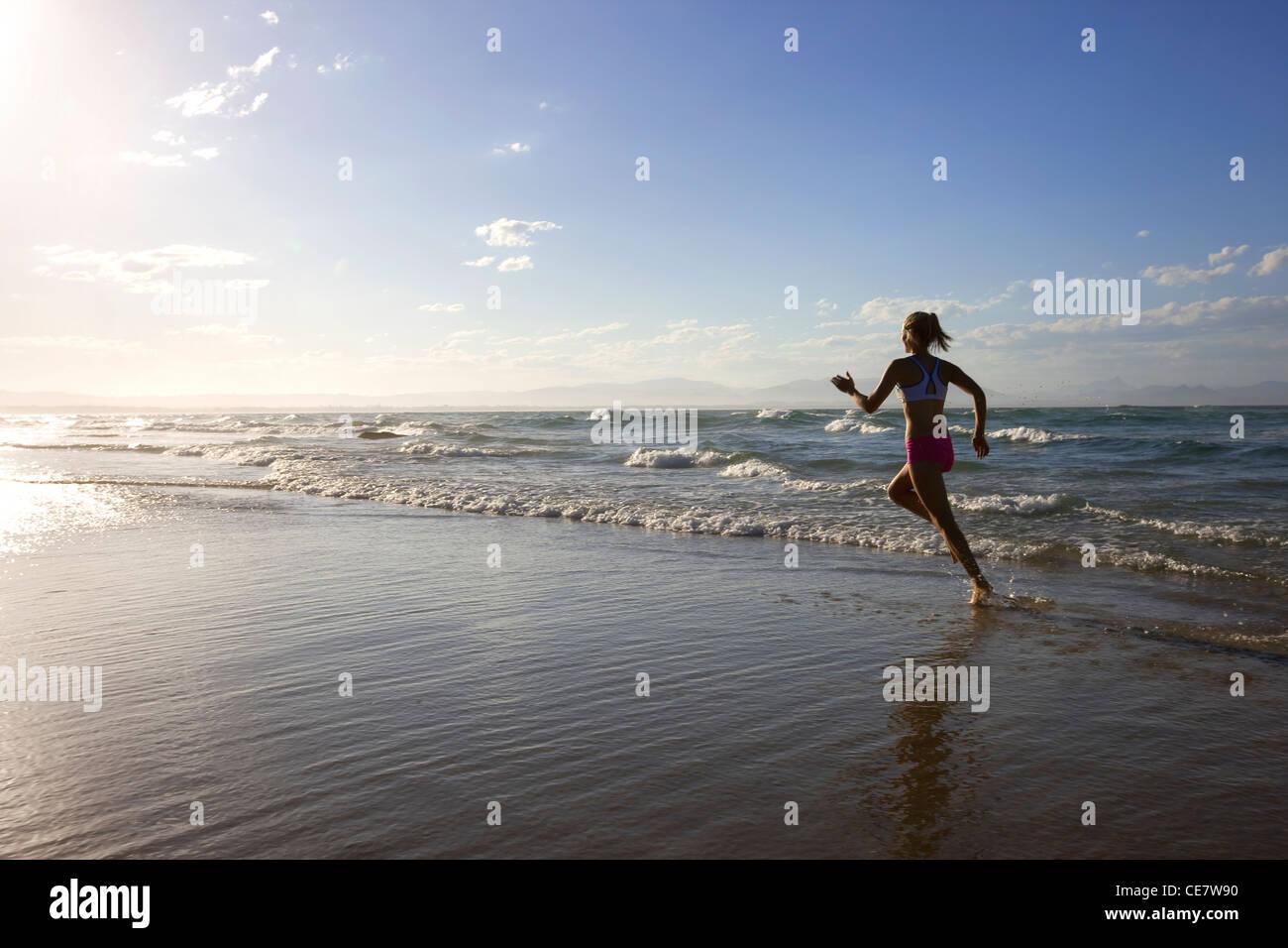 Girl running on the beach - Stock Image
