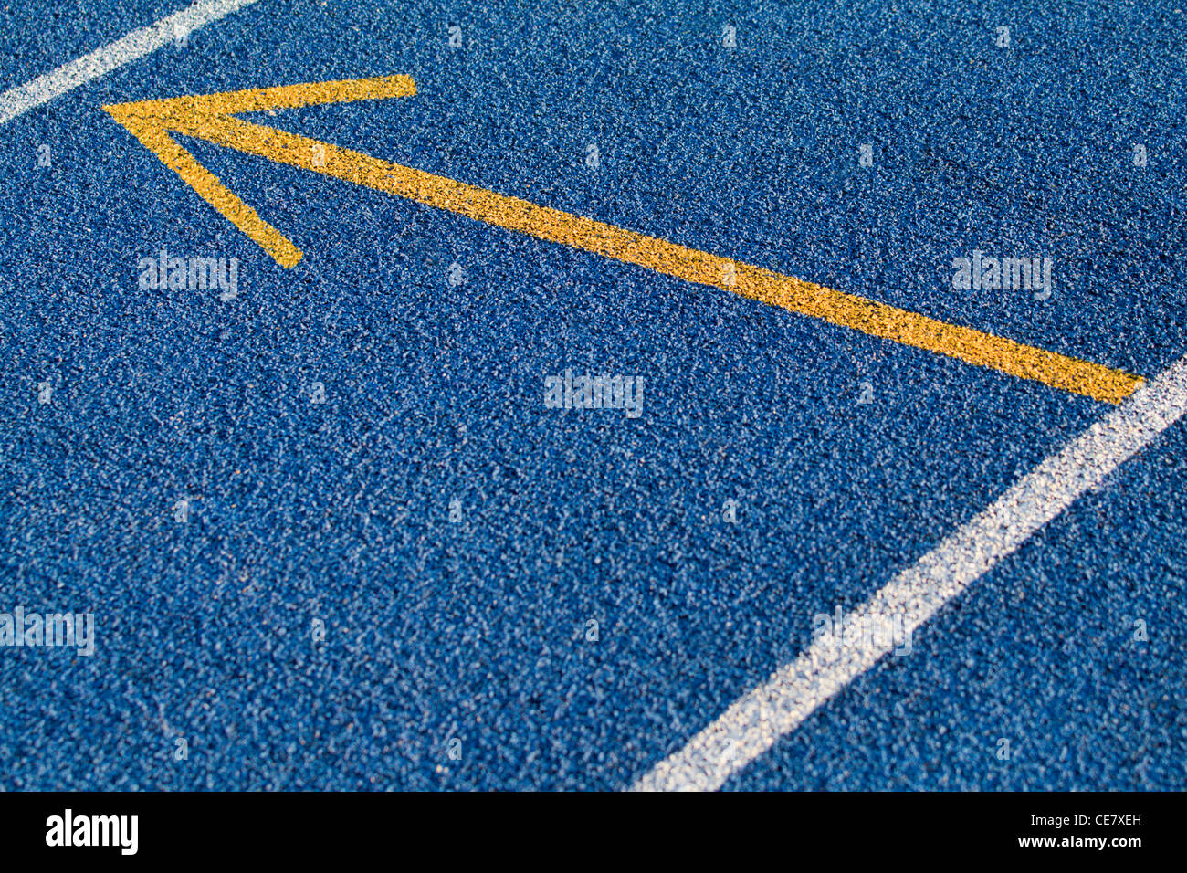 Blue tartan surface with yellow arrow - Stock Image