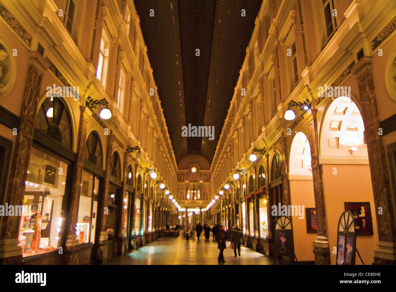 Galeries St Hubert at night a covered arcade with shops and cafes Brussels Belgium EU Europe - Stock Image