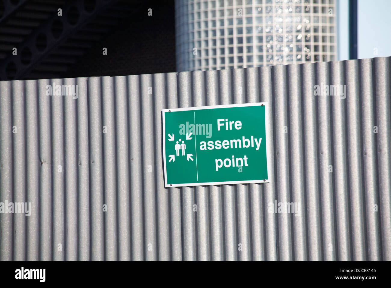 Fire assembly point sign on corrugated iron outside building - Stock Image
