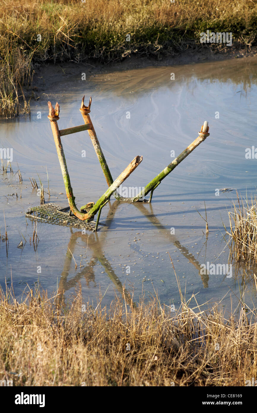 old rusty shopping trolley dumped in the water in Poole - Stock Image