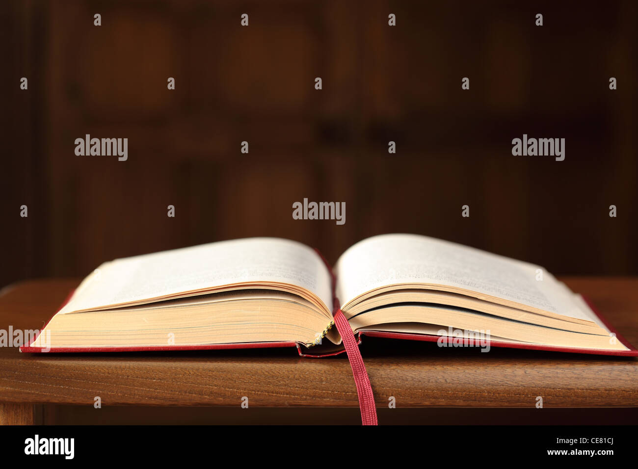 Close up of an open red book on an oak table with blurred background - Stock Image