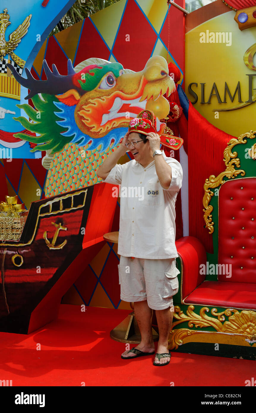 Man trying on a  headdress at a shop dispaly in Bangkok for Chinese New Year. - Stock Image