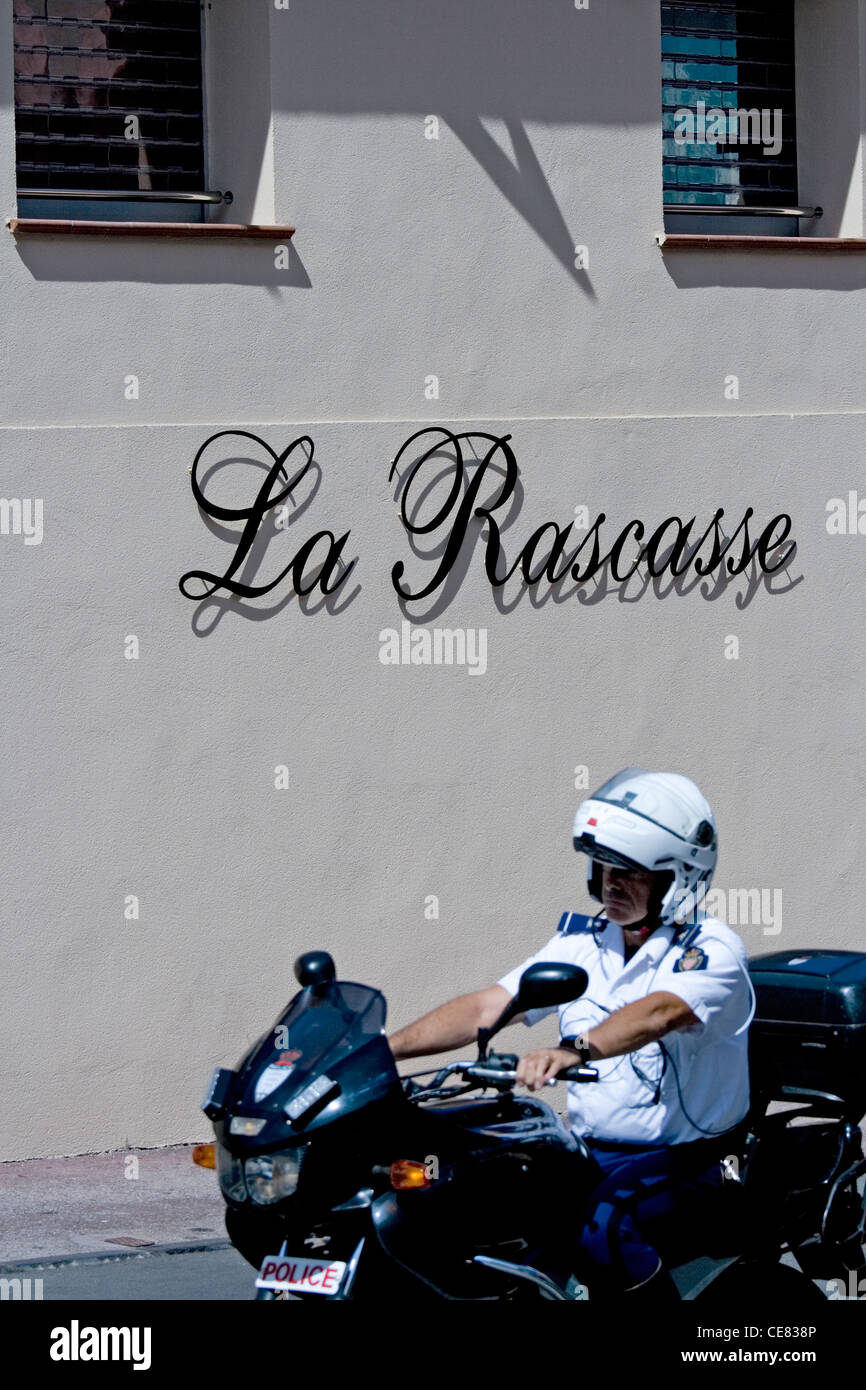 La Rascasse restaurant in Monte Carlo and a famous corner in the Formula 1 race. And a motorcycle policeman riding - Stock Image