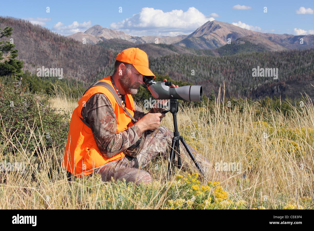 mature adult modern hunter sitting with spotting scope - Stock Image