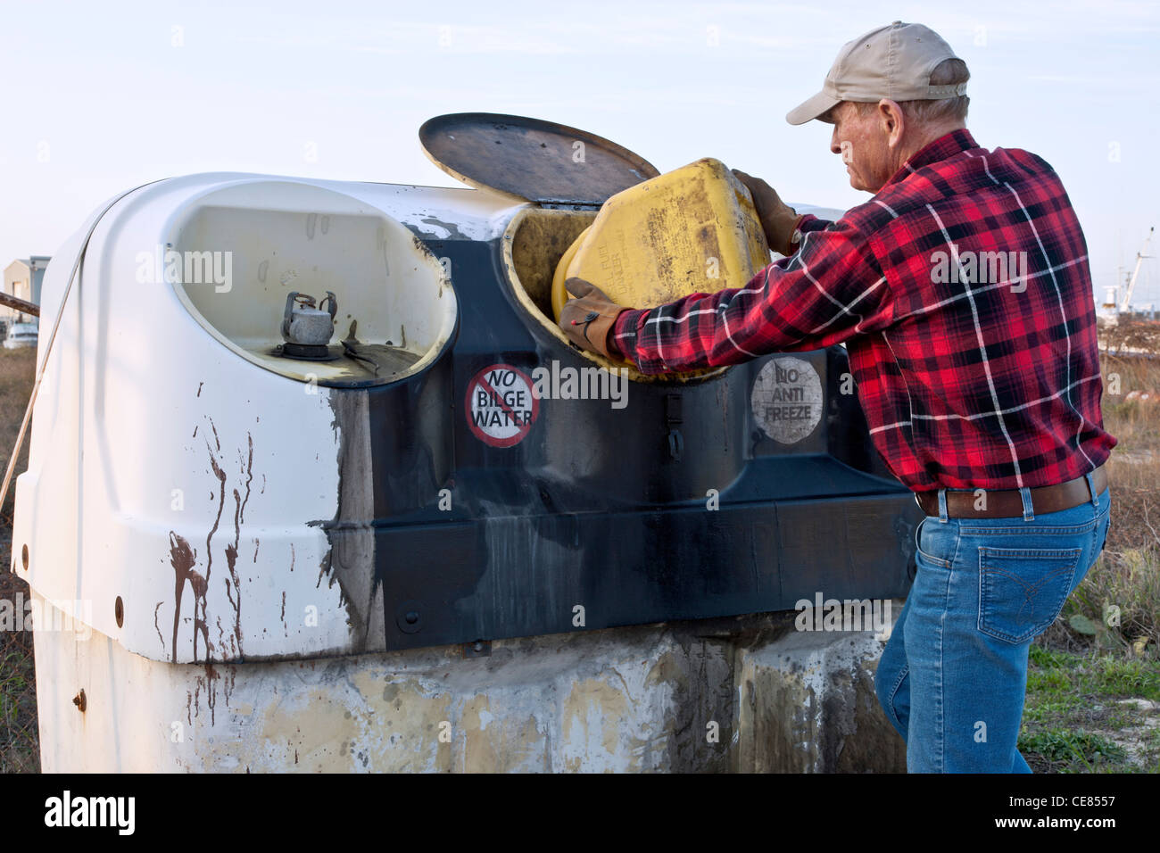 Boat owner depositing used engine oil, Collection Center. - Stock Image