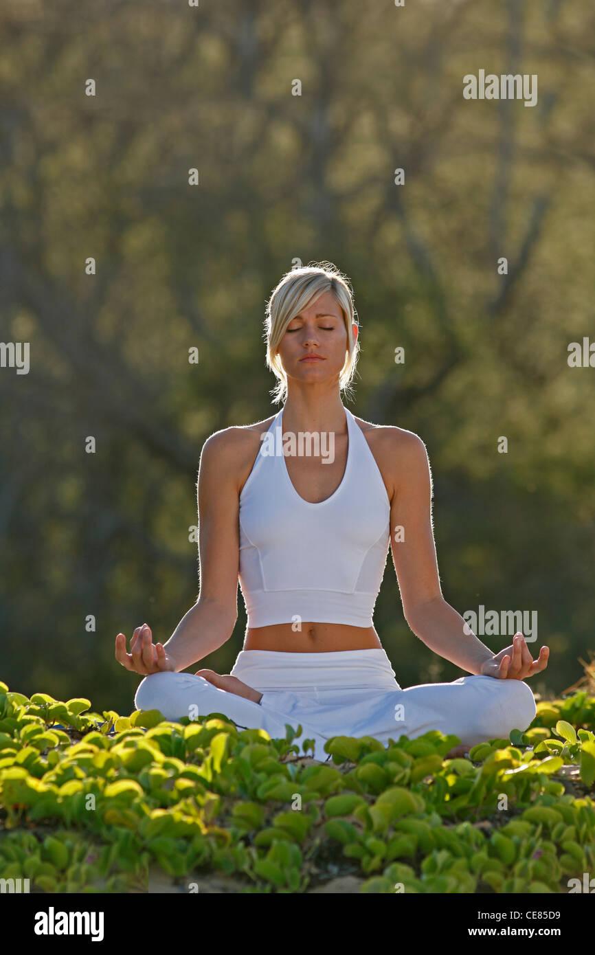 Attractive woman meditates at Makena, Maui, Hawaii. - Stock Image