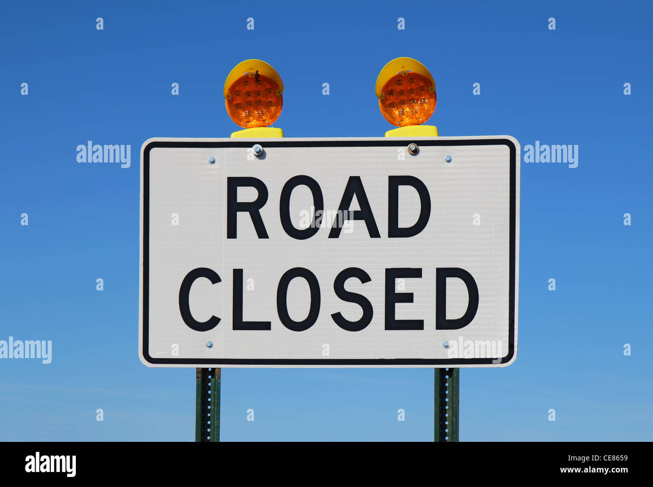 Road closed sign with orange lights against a bright blue sky - Stock Image
