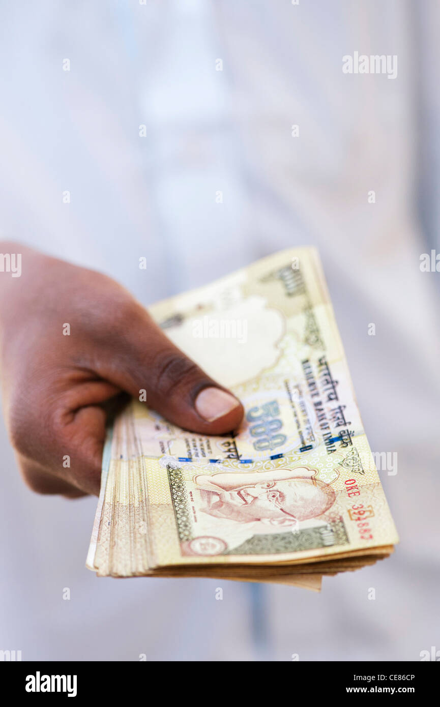 Indian mans hand holding a bunch of 500 rupee notes which were  demonetised in november 2016. India - Stock Image