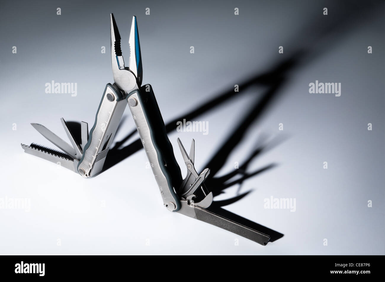 Fully unfolded multitool knife. White foreground, dark background, strong shadow. - Stock Image