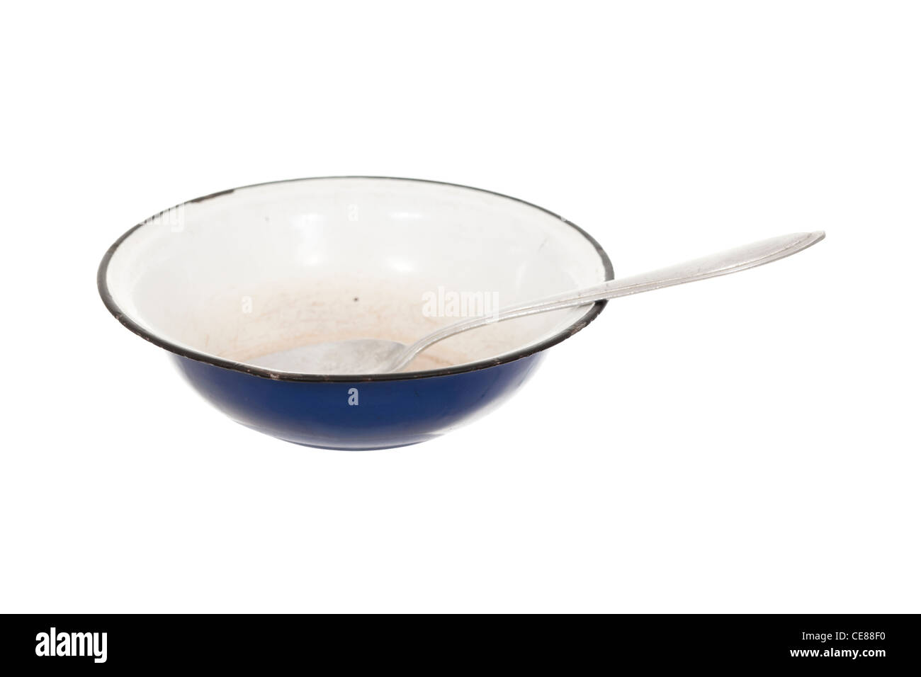 empty bowl with aluminium spoon on white - Stock Image