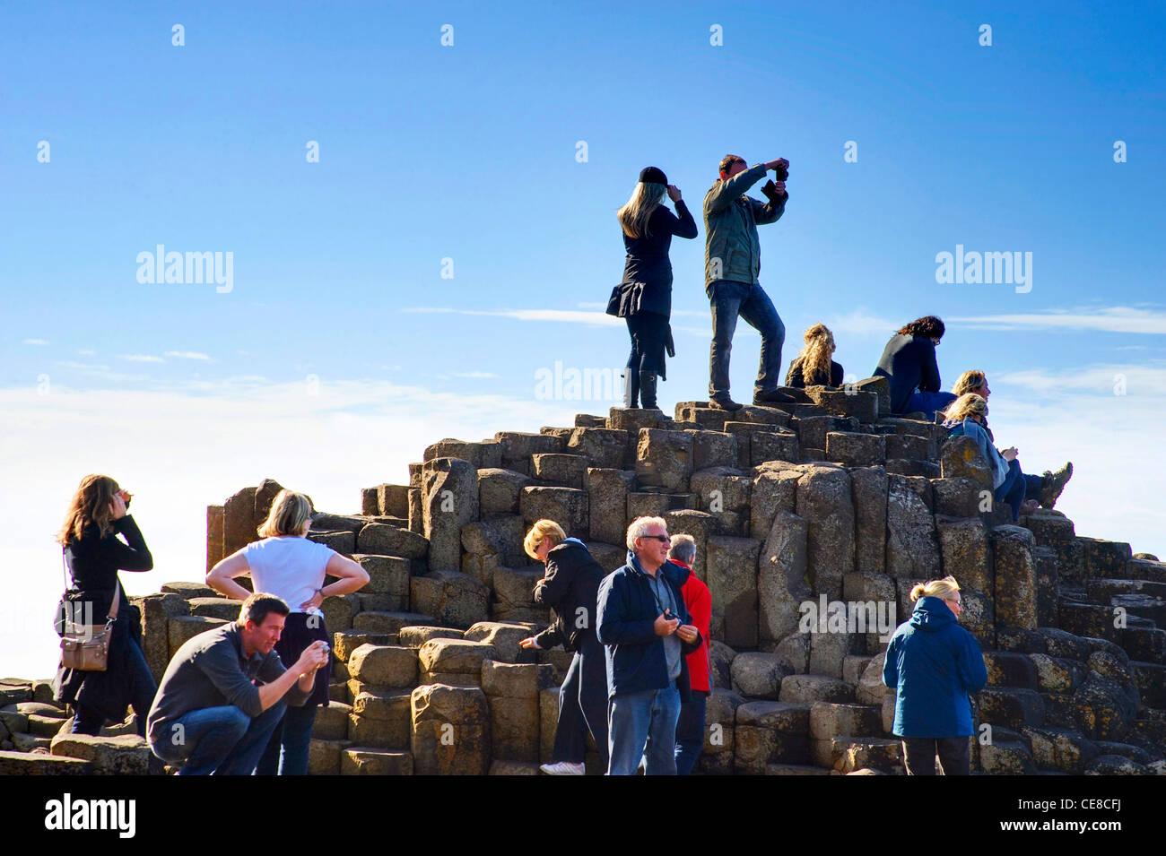 People climbing on the rocks at Giant's Causeway, Northern Ireland Stock Photo