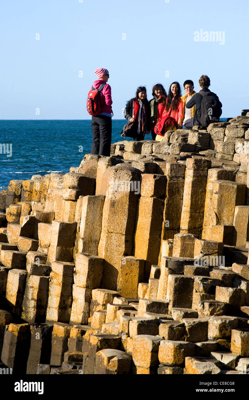 People climbing on the rocks at Giant's Causeway, Northern IrelandStock Photo