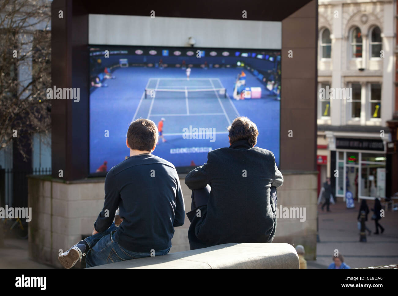Members of the public watch a tennis match on the 'Big Screen' in Victoria Square, Birmingham. - Stock Image