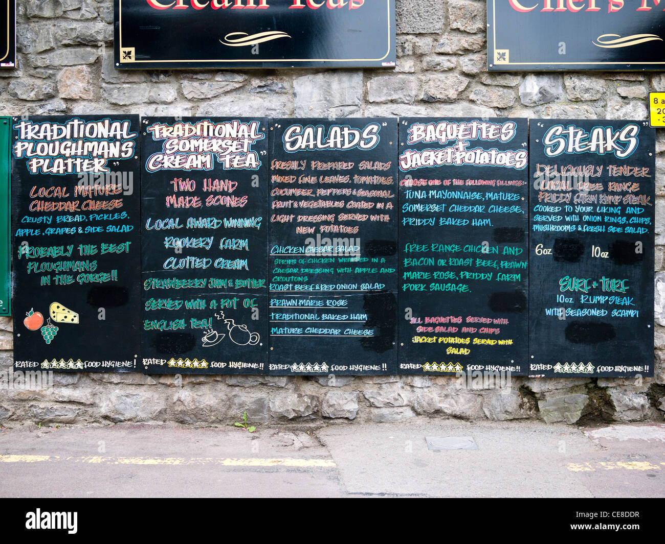 A British pub sign listing the food being served within at the tourist attraction of Cheddar Gorge, Somerset, England. - Stock Image