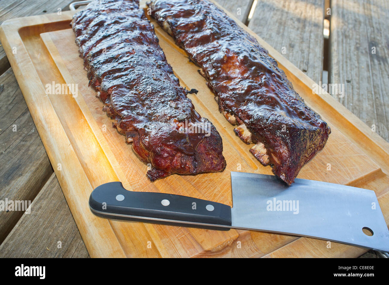 Spare ribs and meat cleaver on a cutting board - Stock Image