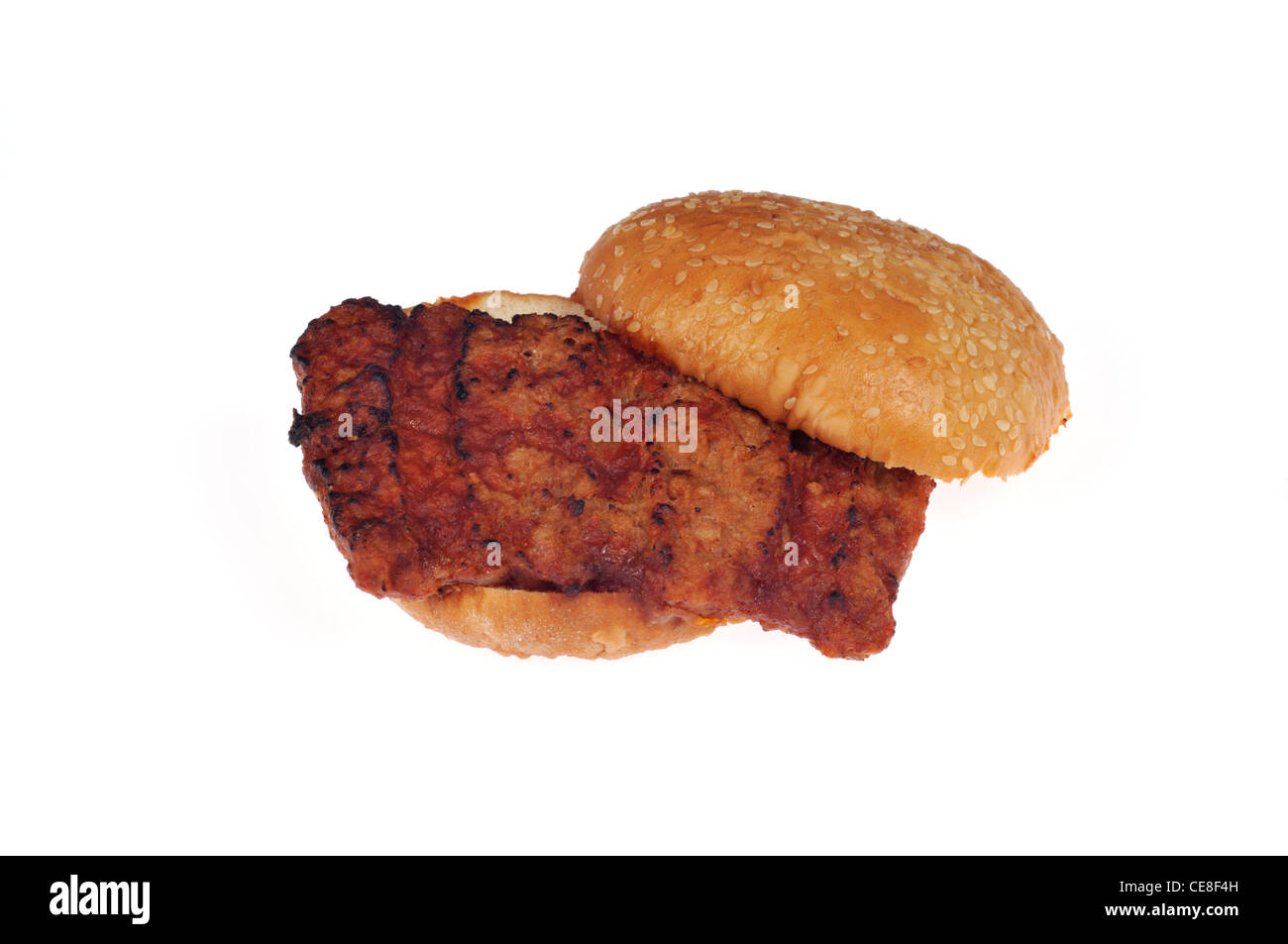 Cooked open BBQ rib pork sandwich on sesame seed roll on white background cut out. - Stock Image