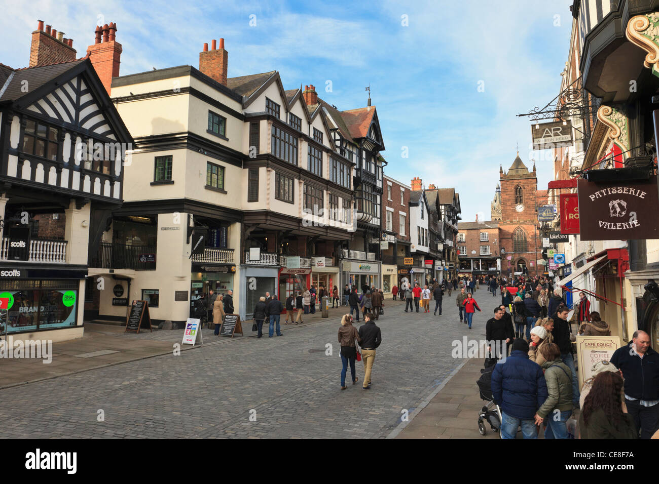 Busy pedestrianised cobbled street scene with shops in historic Tudor buildings in city town centre. Bridge Street - Stock Image