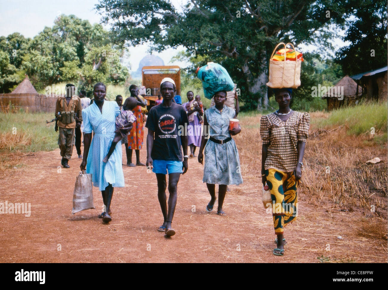 Villagers in Southern Sudan carrying items back from a market - Stock Image