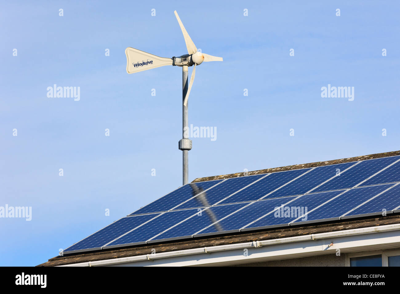 Windsave micro wind turbine and solar panels on a domestic eco home house roof for power generation with alternative - Stock Image
