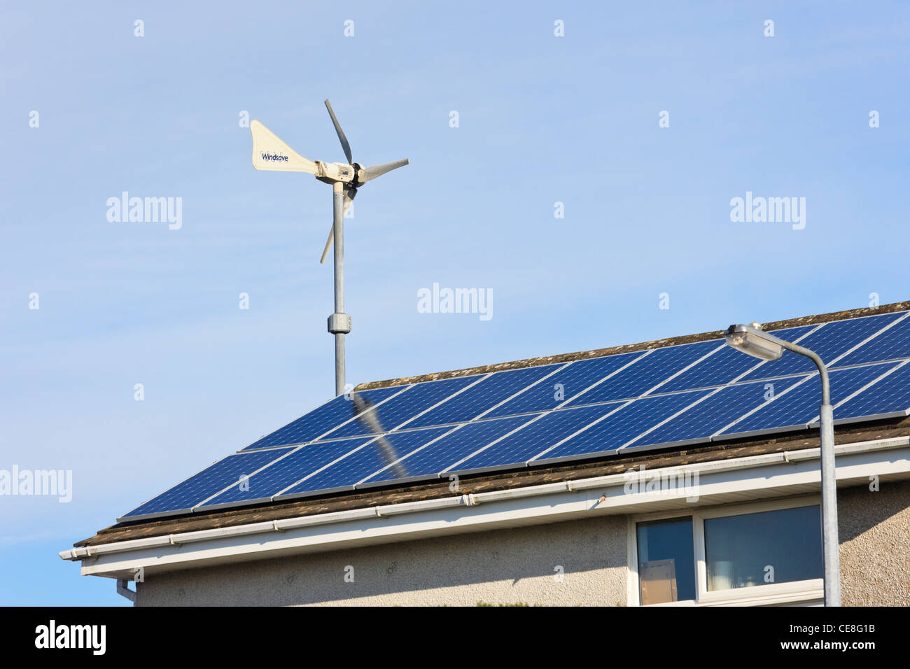 Windsave micro wind turbine and solar panels on a house roof providing cheap electricity alternative energy power - Stock Image