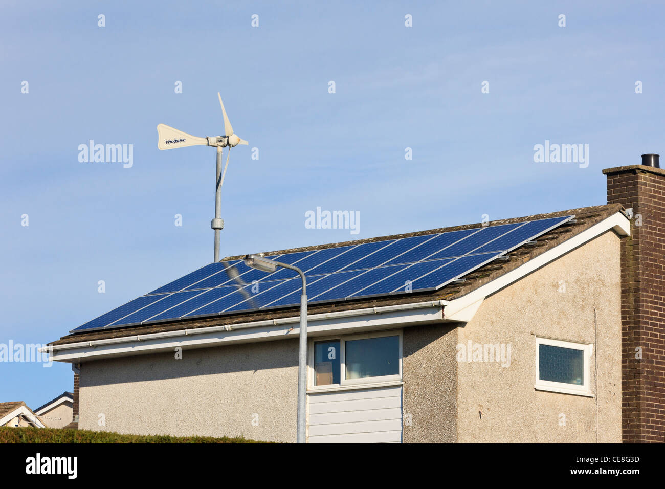 Windsave micro wind turbine and solar panels on a domestic eco home house roof for alternative energy. UK - Stock Image