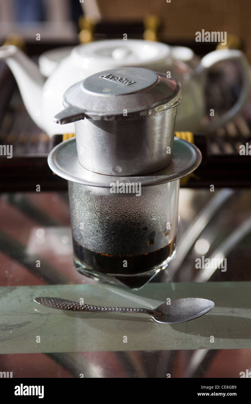 Vietnamese Coffee filter with glass and accompanying tea - Stock Image