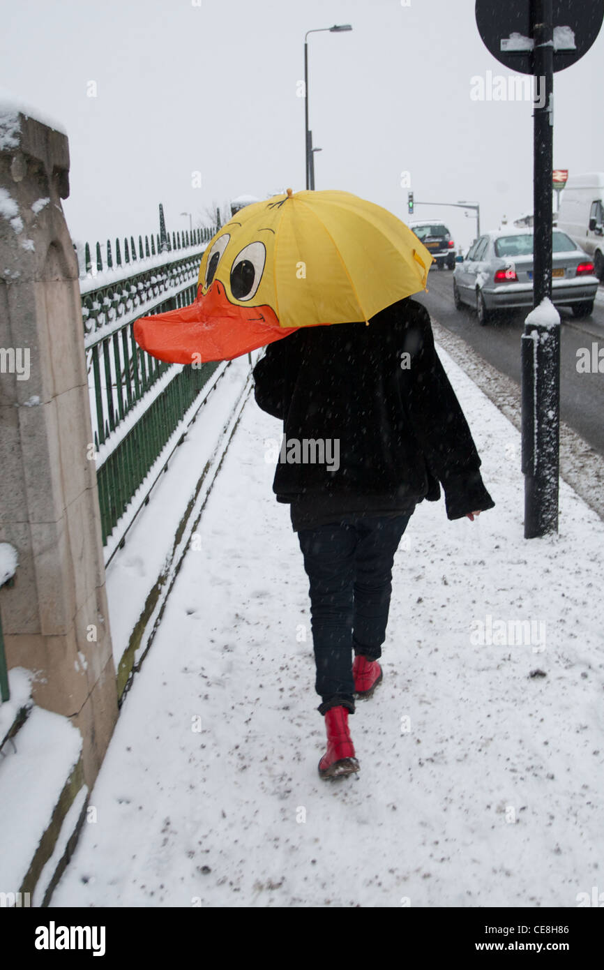 A Woman Crosses Bridge In The Snow With Bright Coloured Duck Umbrella Protecting Her
