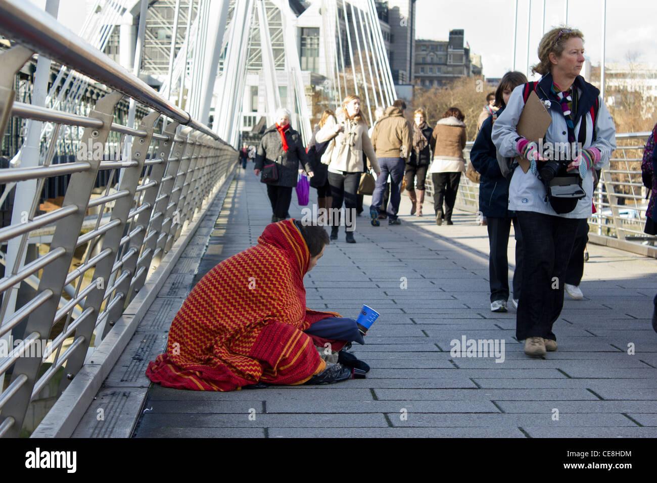 man wrapped in blanket begging on Golden Jubilee Bridge, London, UK - Stock Image