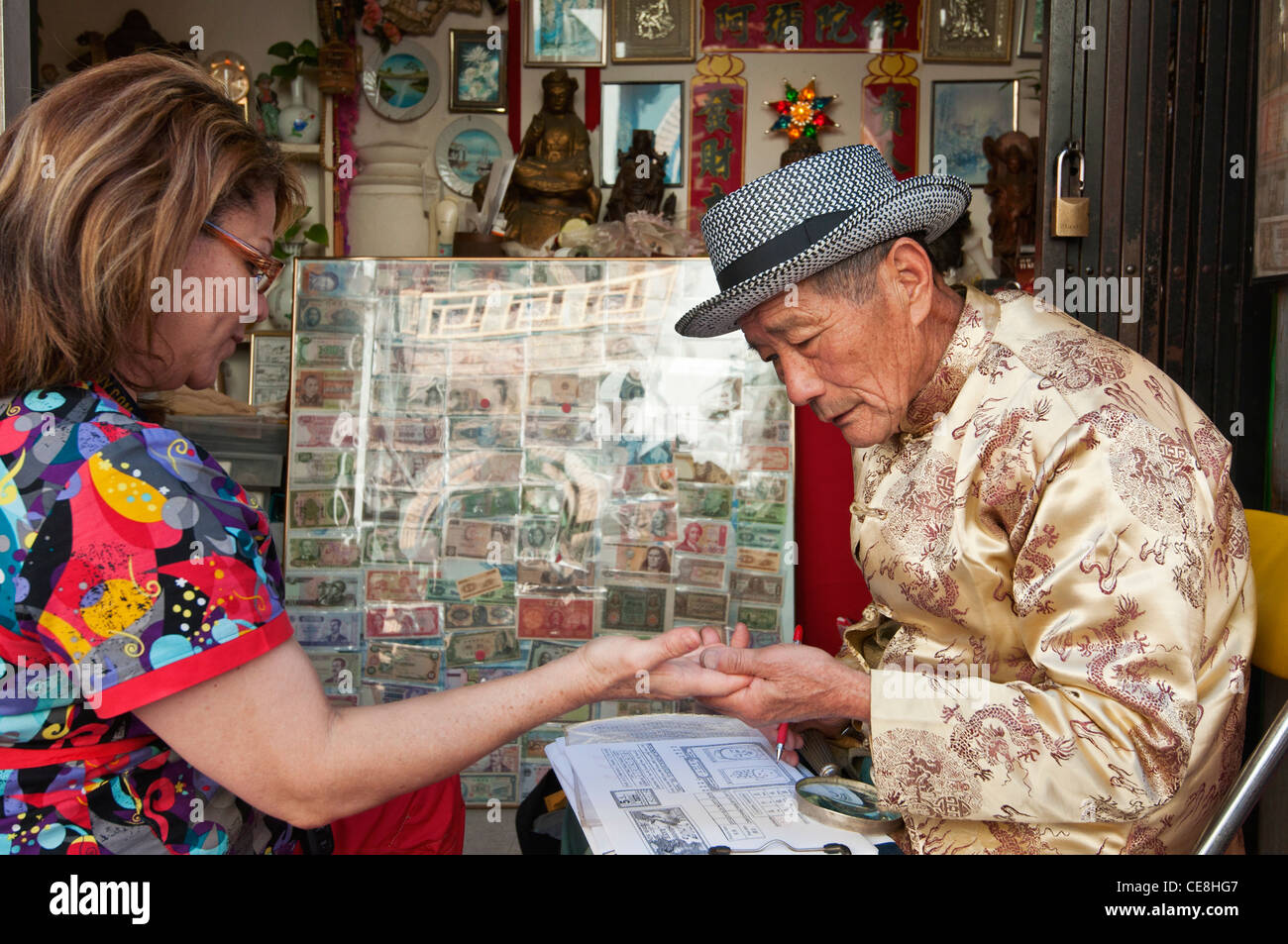 People getting their palms read for their fortune by Leo at the It Pun Fortune Readings in Los Angeles, Chinatown. - Stock Image