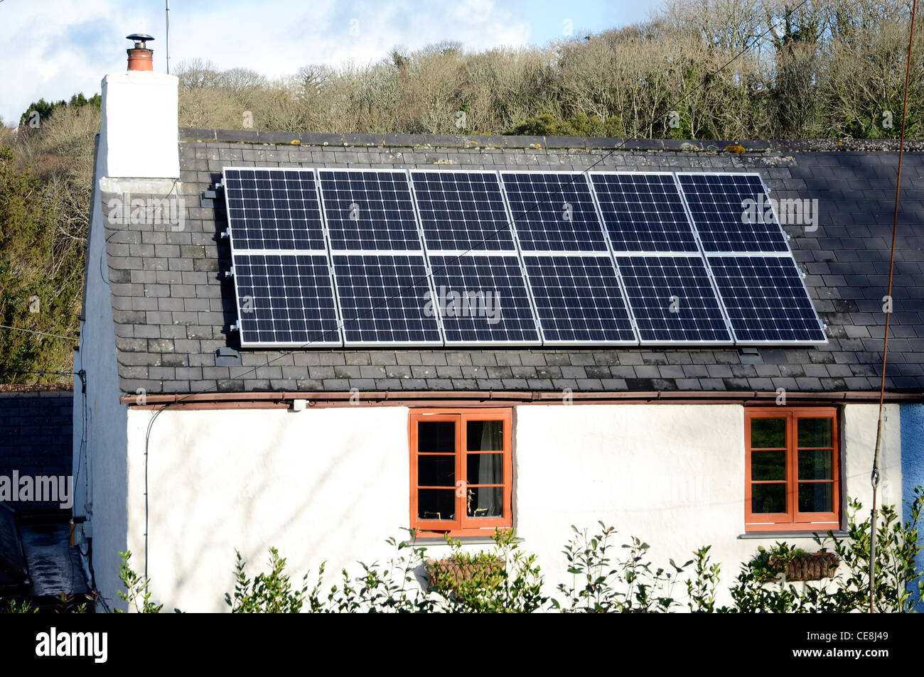 Solar panels fitted to the roof of an old cottage - Stock Image