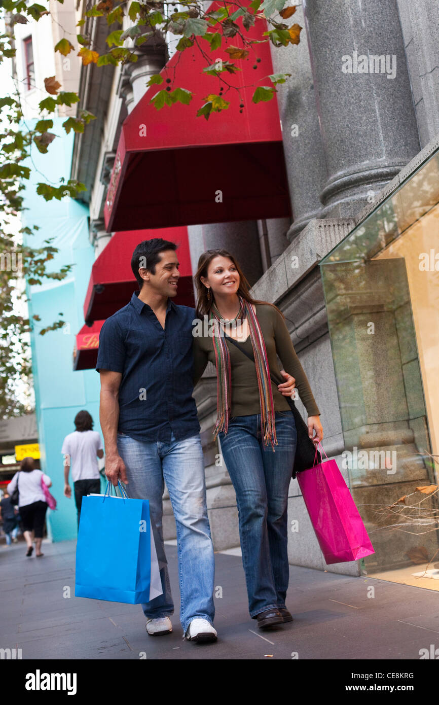 Couple with shopping bags looking in shop windows. Collins Street, Melbourne, Victoria, Australia - Stock Image