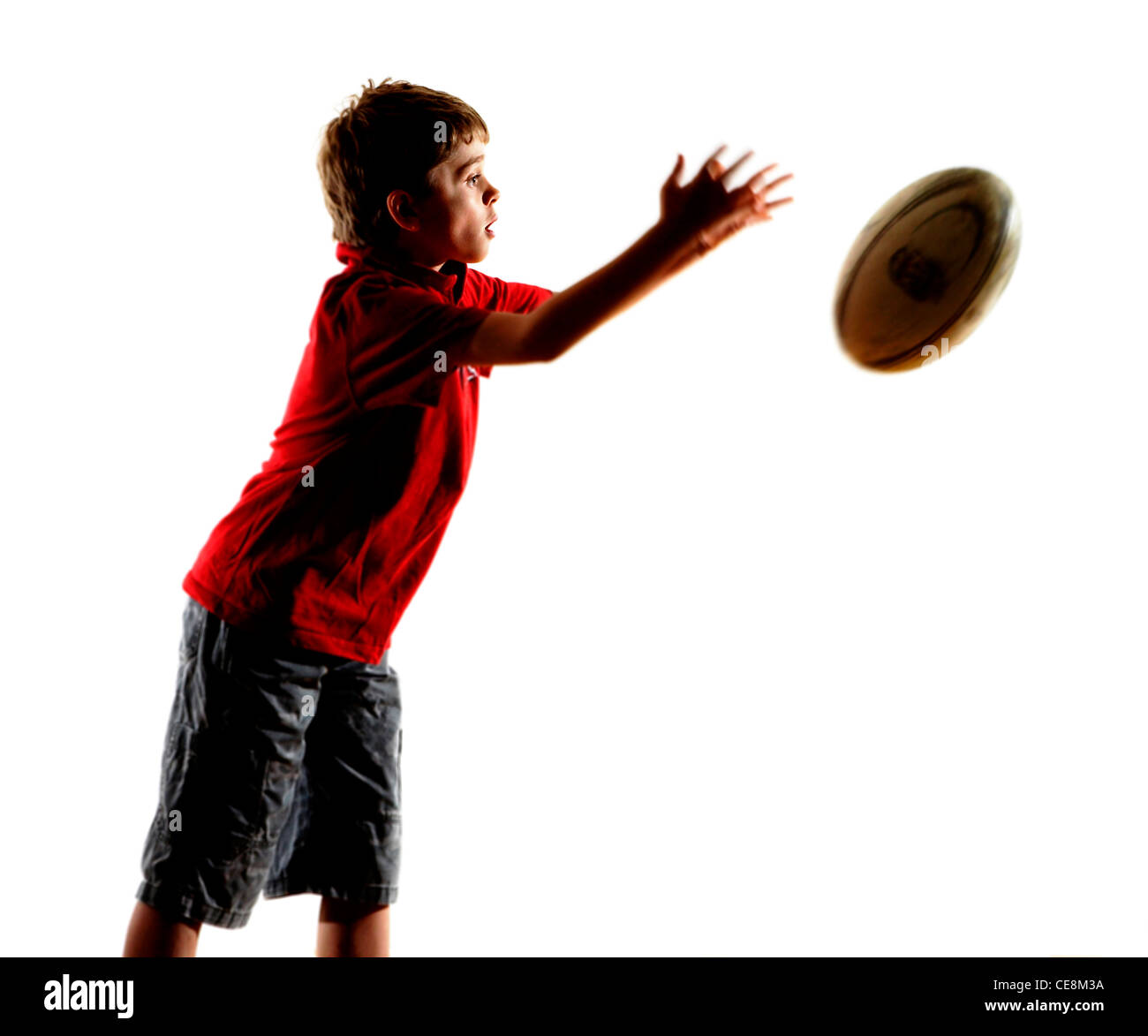 Young child (8) throw a rugby ball in the studio - Stock Image