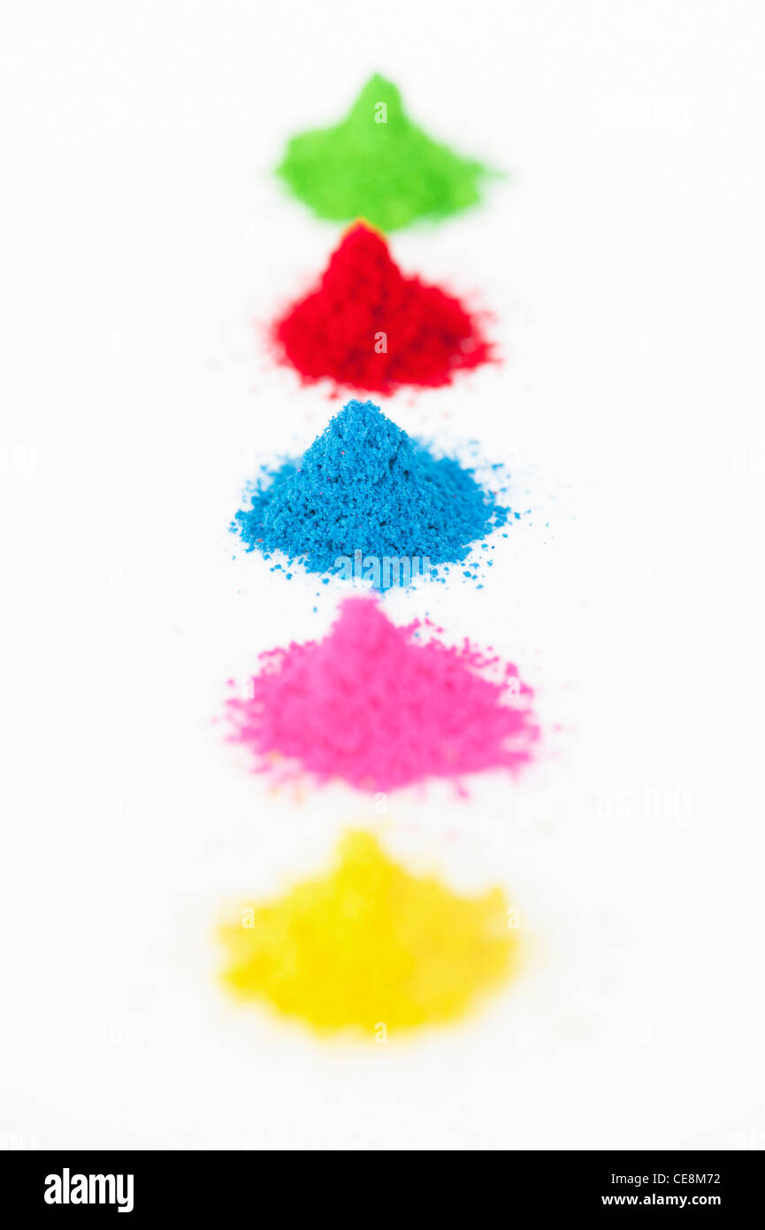 Piles of coloured Indian powder used for making rangoli designs. White Background - Stock Image