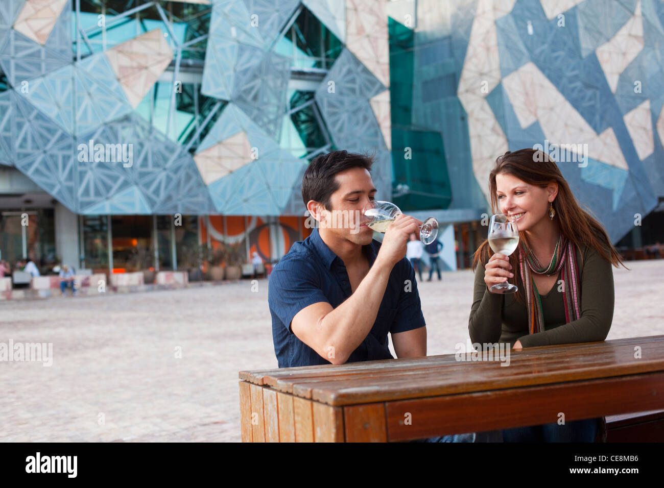Young couple enjoying drink at an outdoor bar federation square melbourne victoria australia