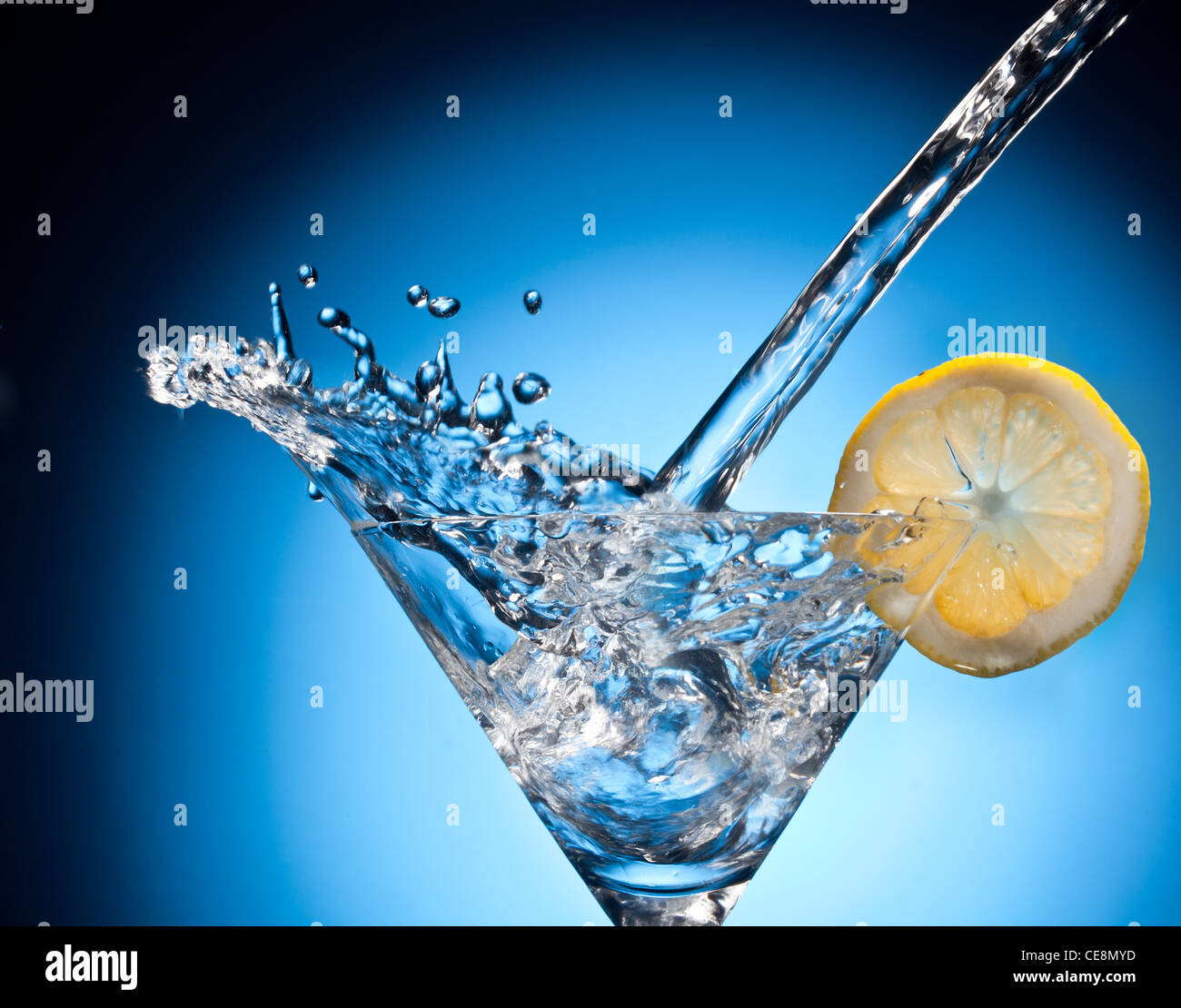 Splash from pouring martini into the glass. Object on a blue background. - Stock Image