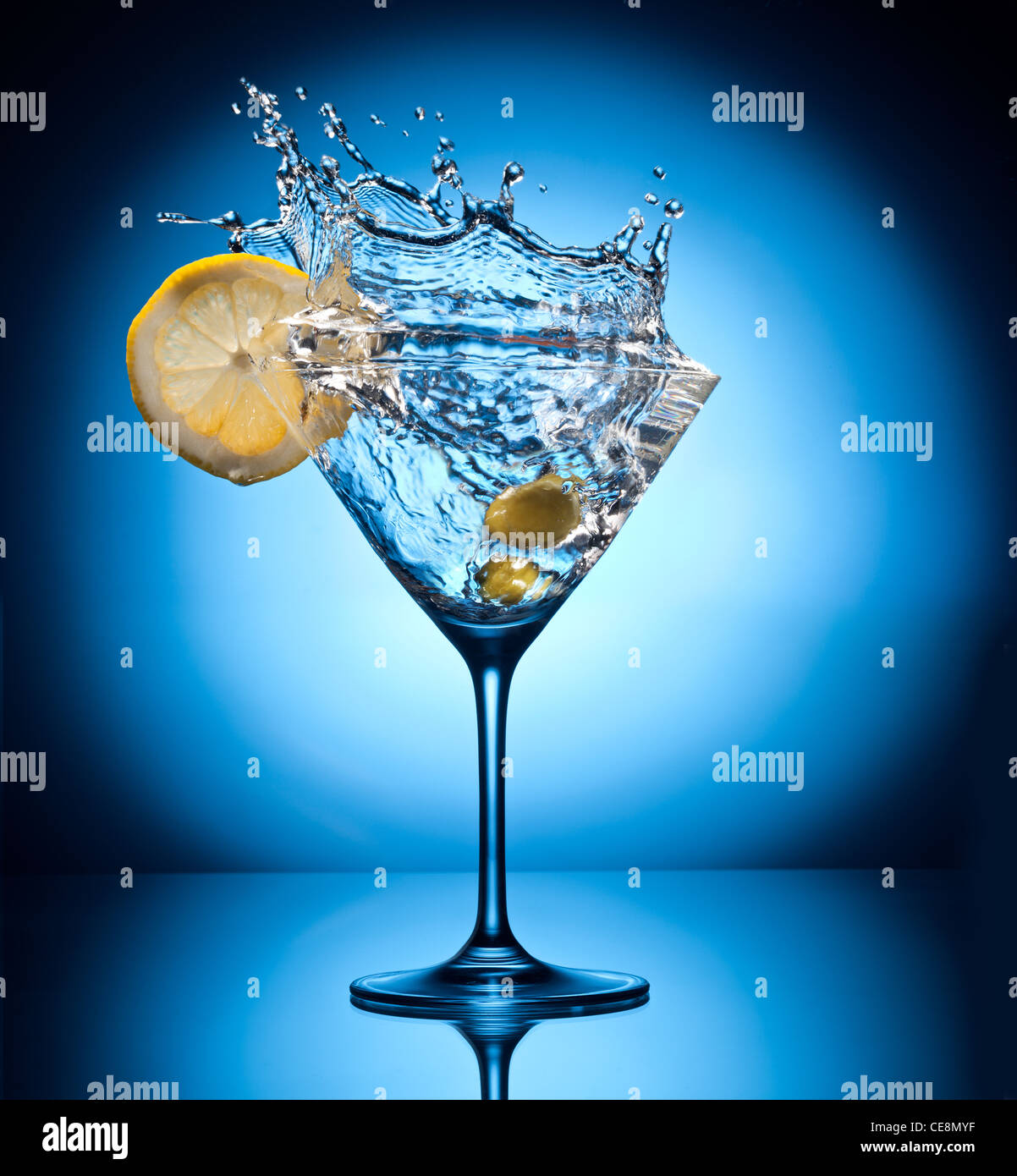 Splash martini from flying olives. Object on a blue background. - Stock Image