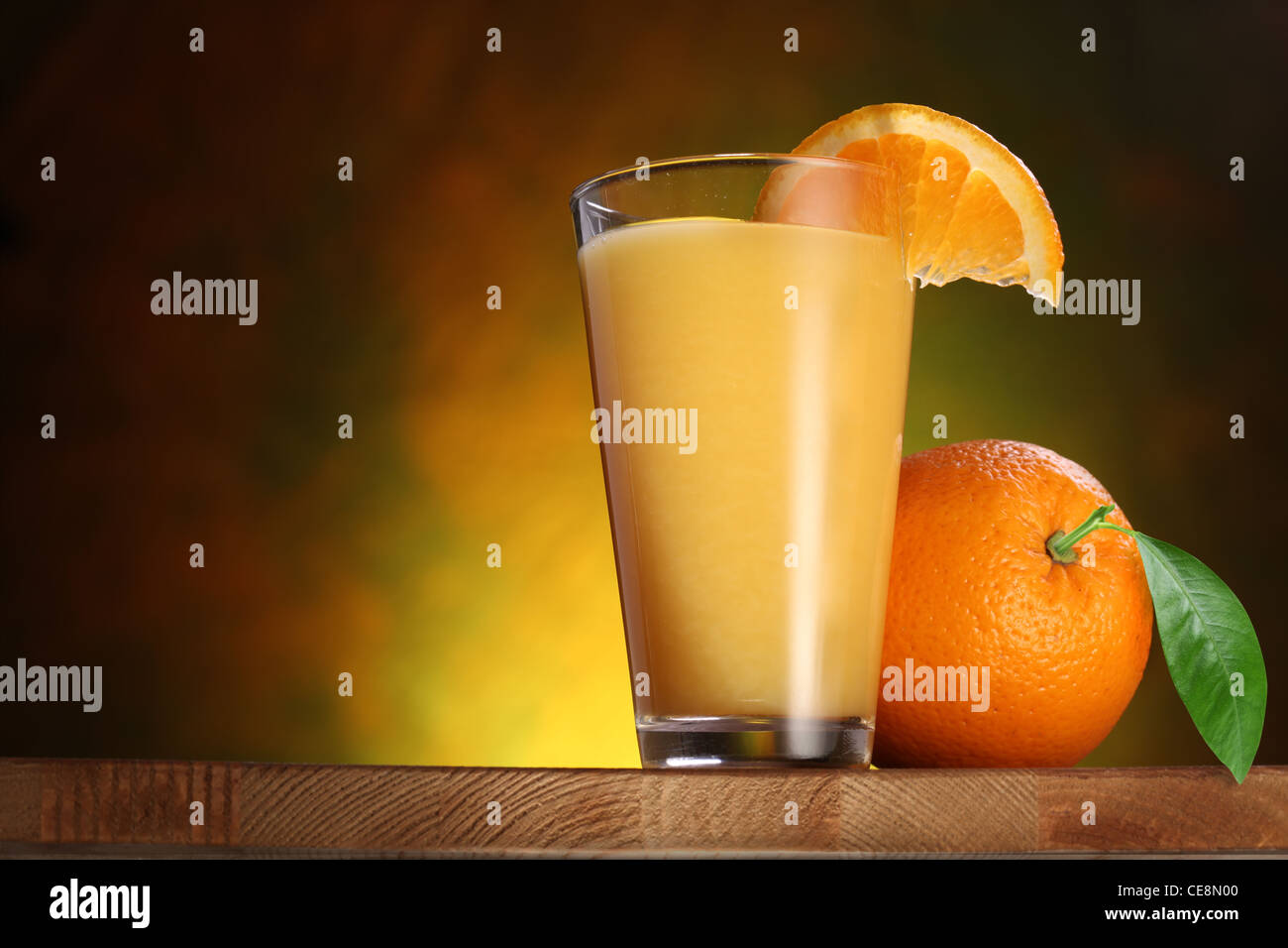 Oranges and glass of juice on a wooden table. - Stock Image