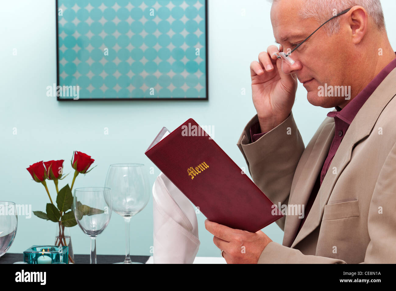 Photo of a man reading the menu in a restaurant - Stock Image
