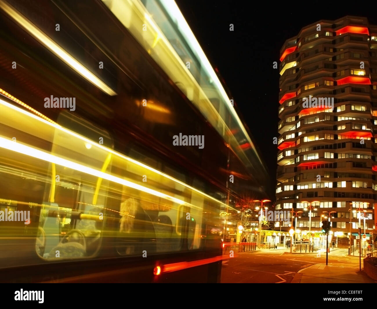A bus passes, leaving light trails in its wake. In the background is the illuminated officeblock of Croydon No.1 - Stock Image