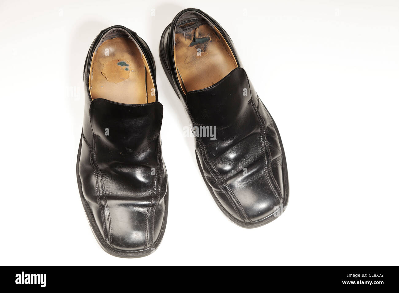 Pair of old worn out gents black shoes photographed on white - Stock Image