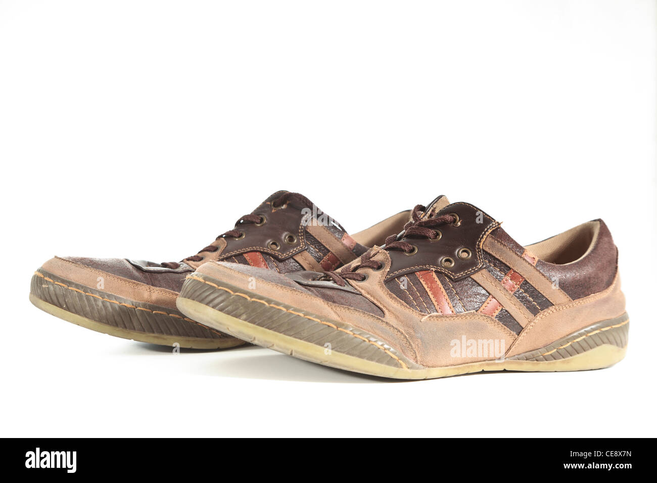Pair of old worn out shoes photographed on a white background - Stock Image