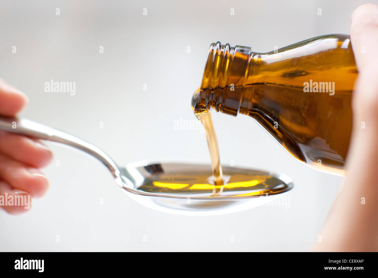 MODEL RELEASED. Pouring medicine. - Stock Image