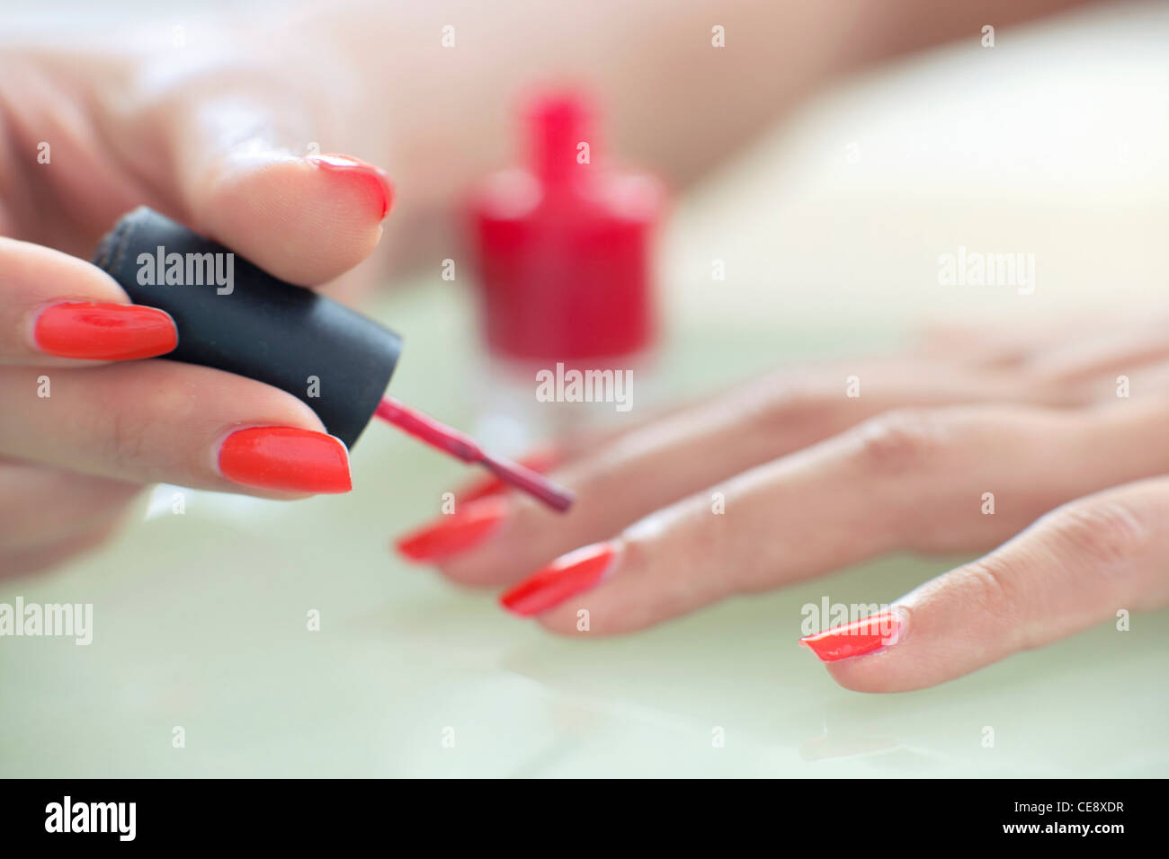 MODEL RELEASED. Woman painting her nails. - Stock Image