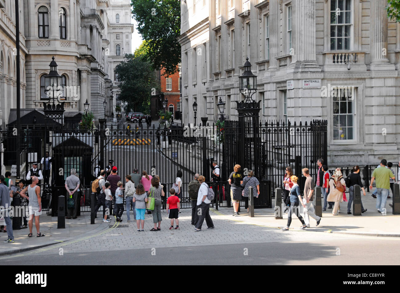 Tourists on the Whitehall side of Downing Street in front of steel security gates controlled by Metropolitan police - Stock Image
