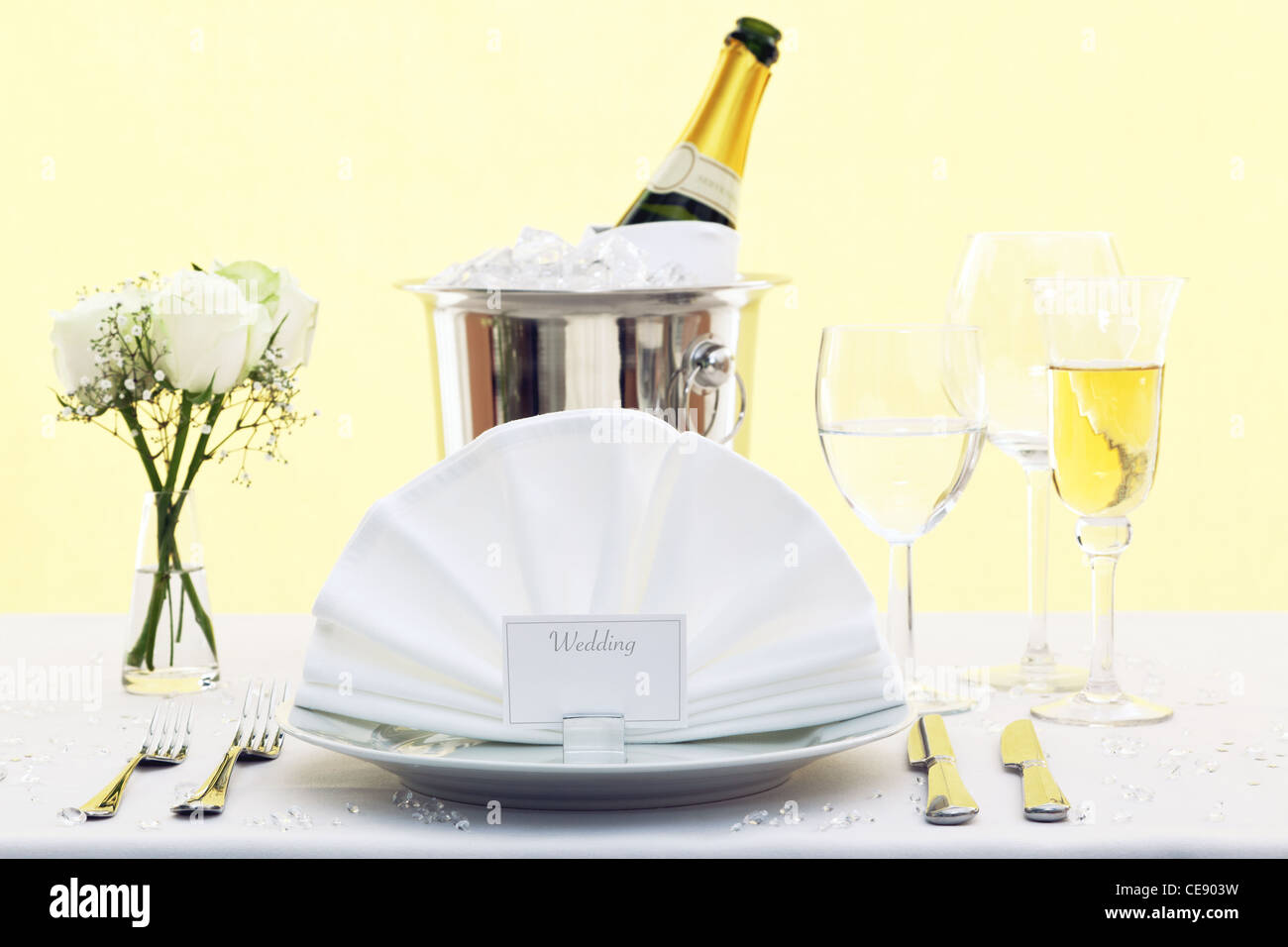 Photo of a wedding table place setting with place card and a bottle of chilled champagne in an ice bucket. - Stock Image